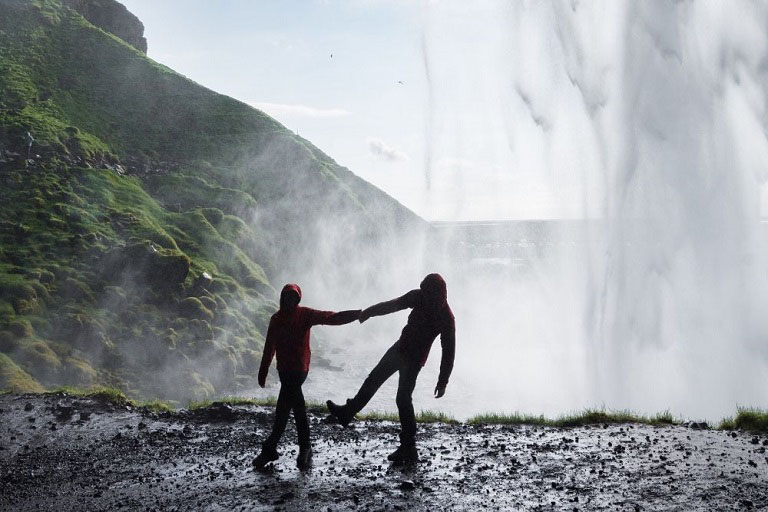 Couple dancing under waterfull in Iceland