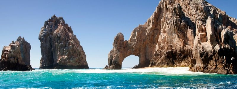 body of water near brown rock formation in cabos san lucas mexico