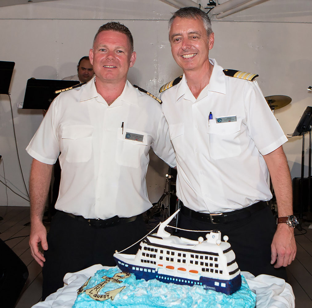 Captain Carl poses with Hotel Director Phillip and the cake.