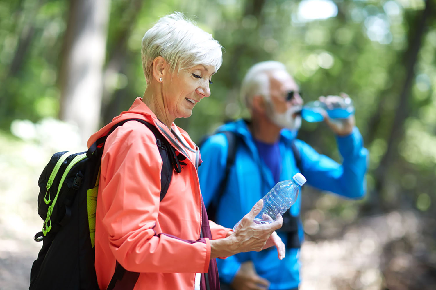 A man and woman out exploring nature each drink a bottle of water