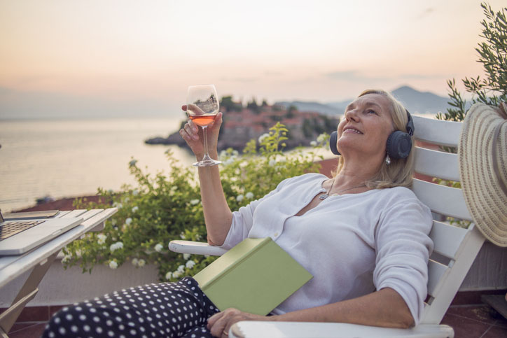 Woman enjoying on the balcony listening to music