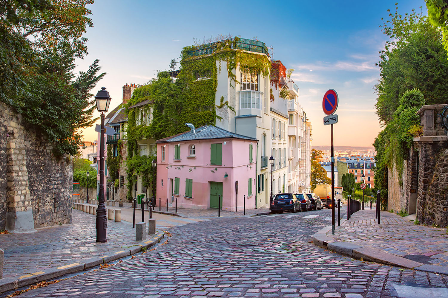 Cozy old street with pink house at the sunny sunrise in Paris, France