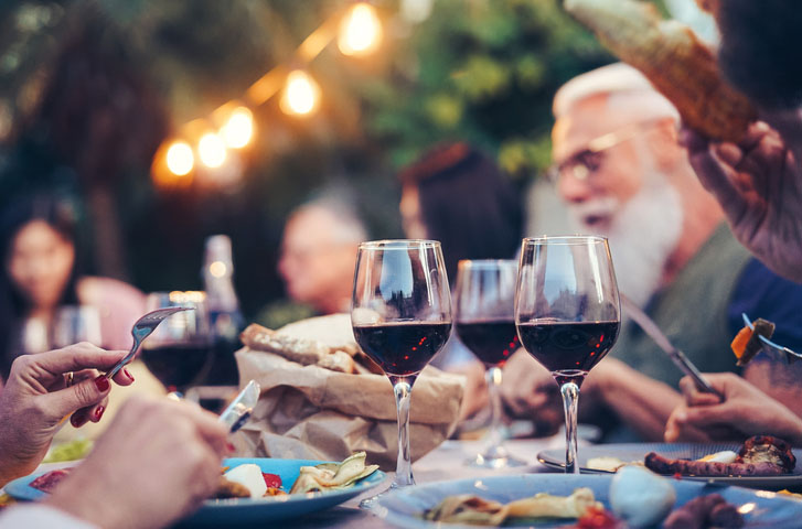 People gathered around a dinner table with glasses of wine