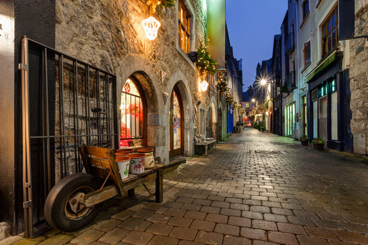 lights decorate an old street in Galway, Ireland in the evening