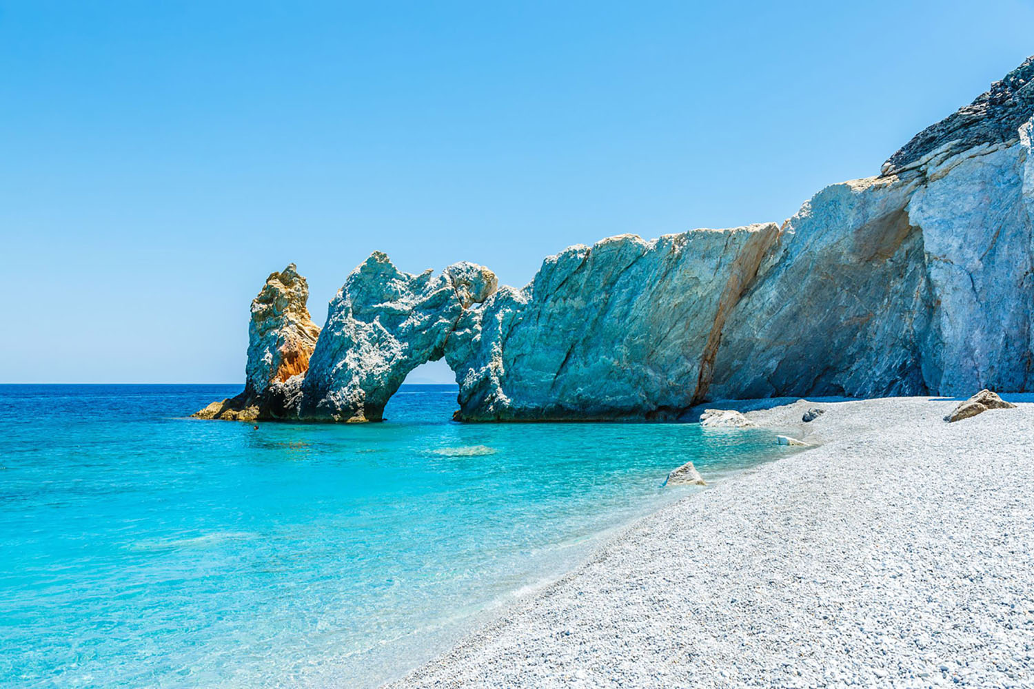 Famous hole in the rock formation at Lalaria beach in Skiathios, Greece.