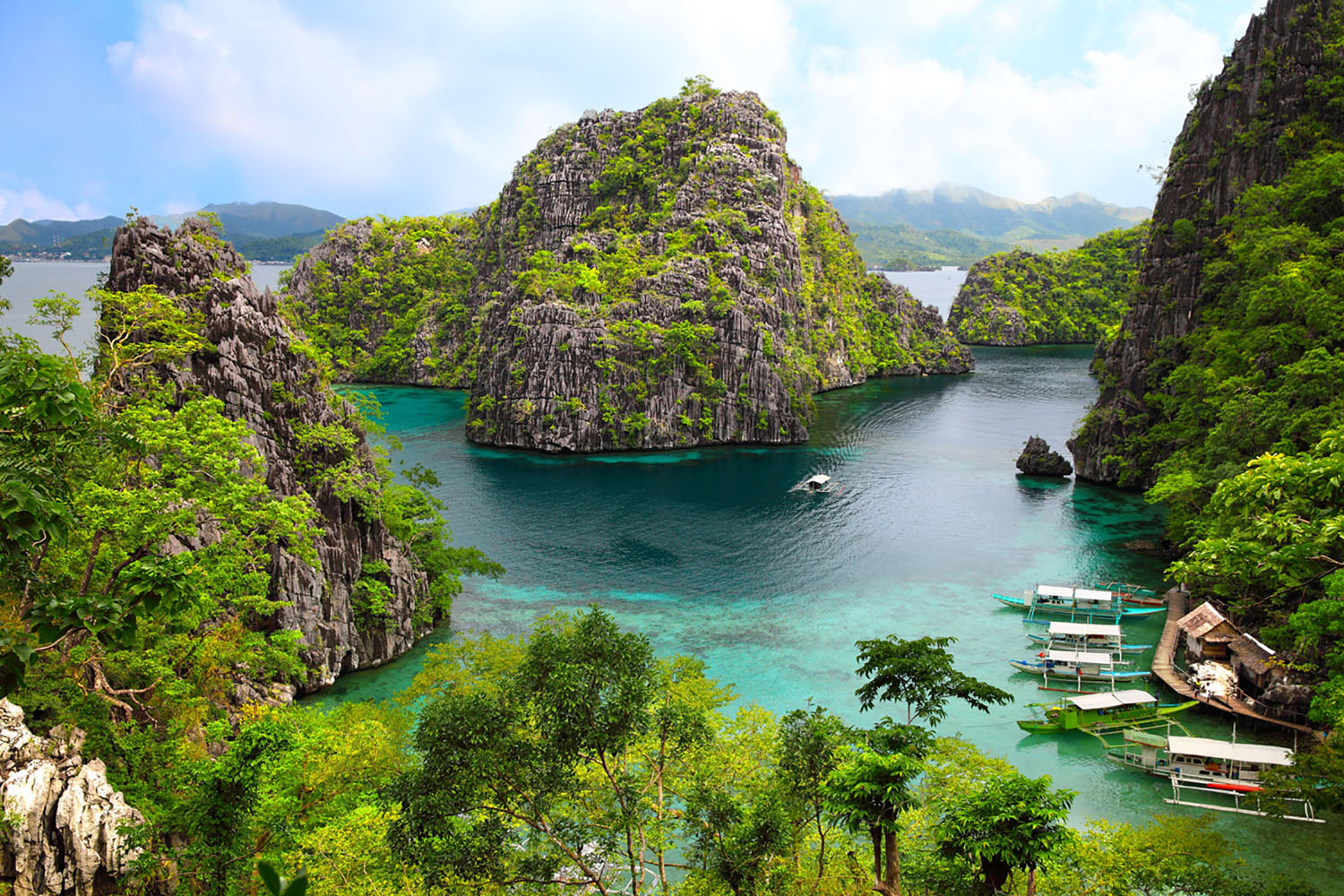 A blue lagoon surrounded by towering cliffs in Coron, Philippines