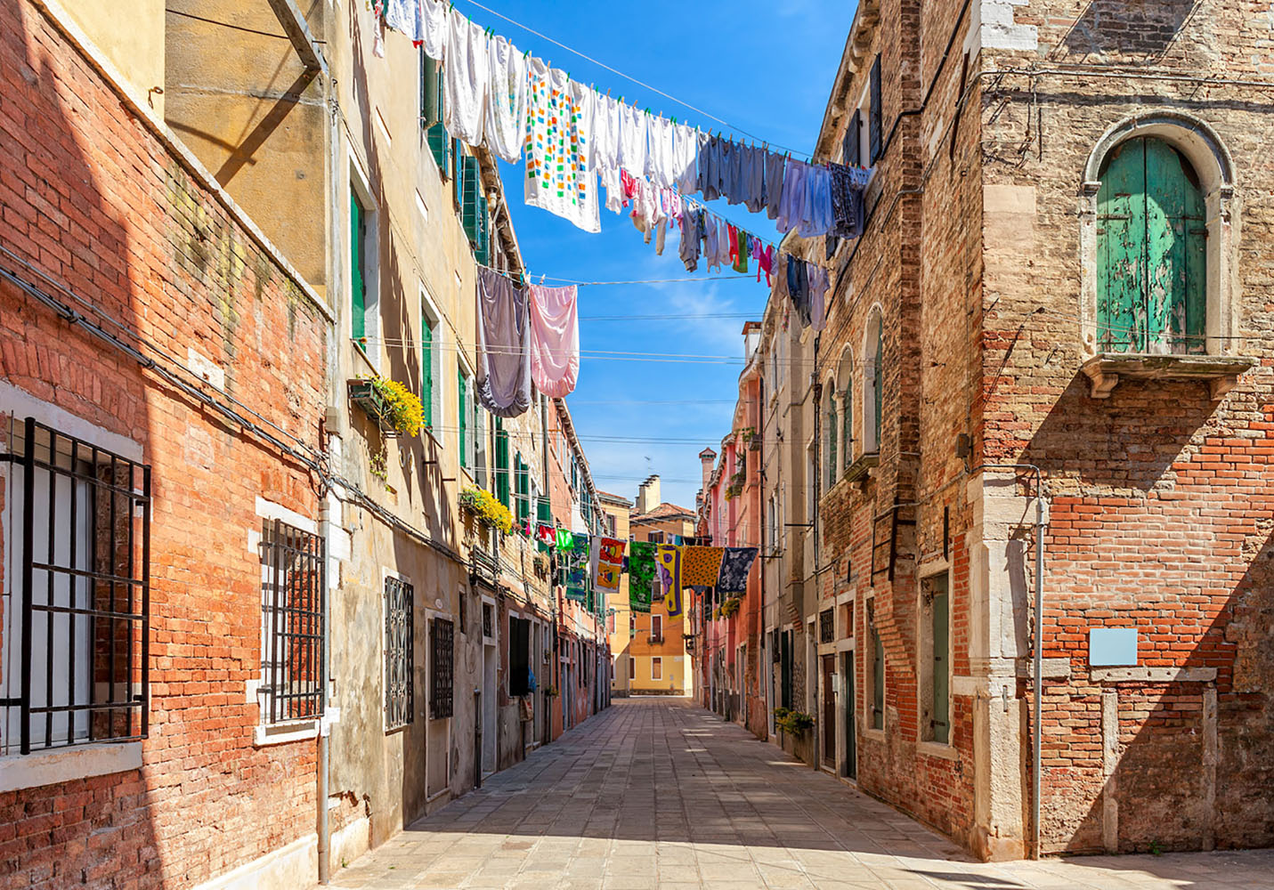 Laundry hangs from homes on a quiet street in Venice, Italy.