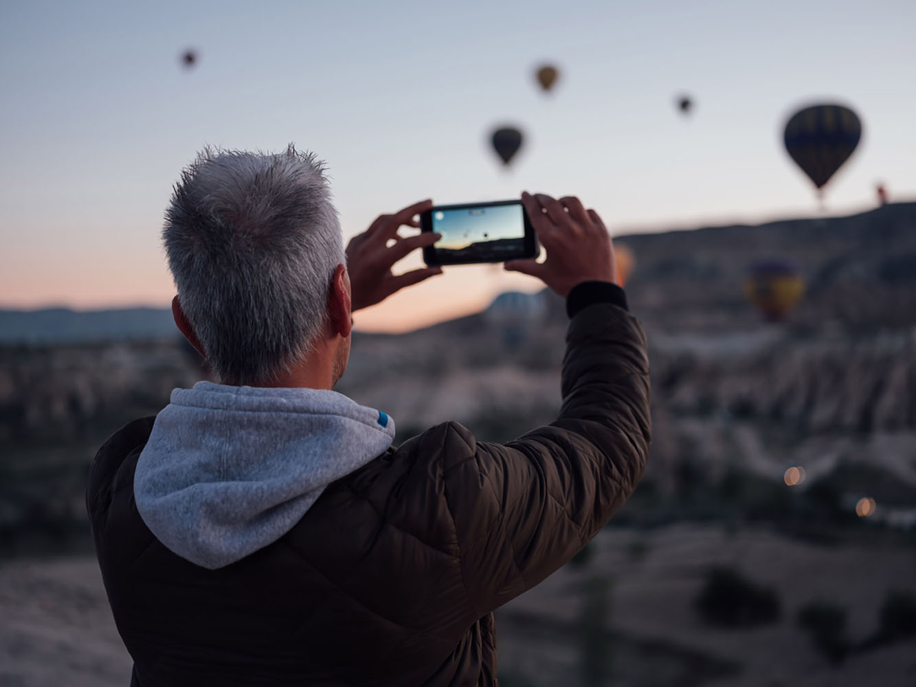 A man takes photos of hot air balloons using his phone