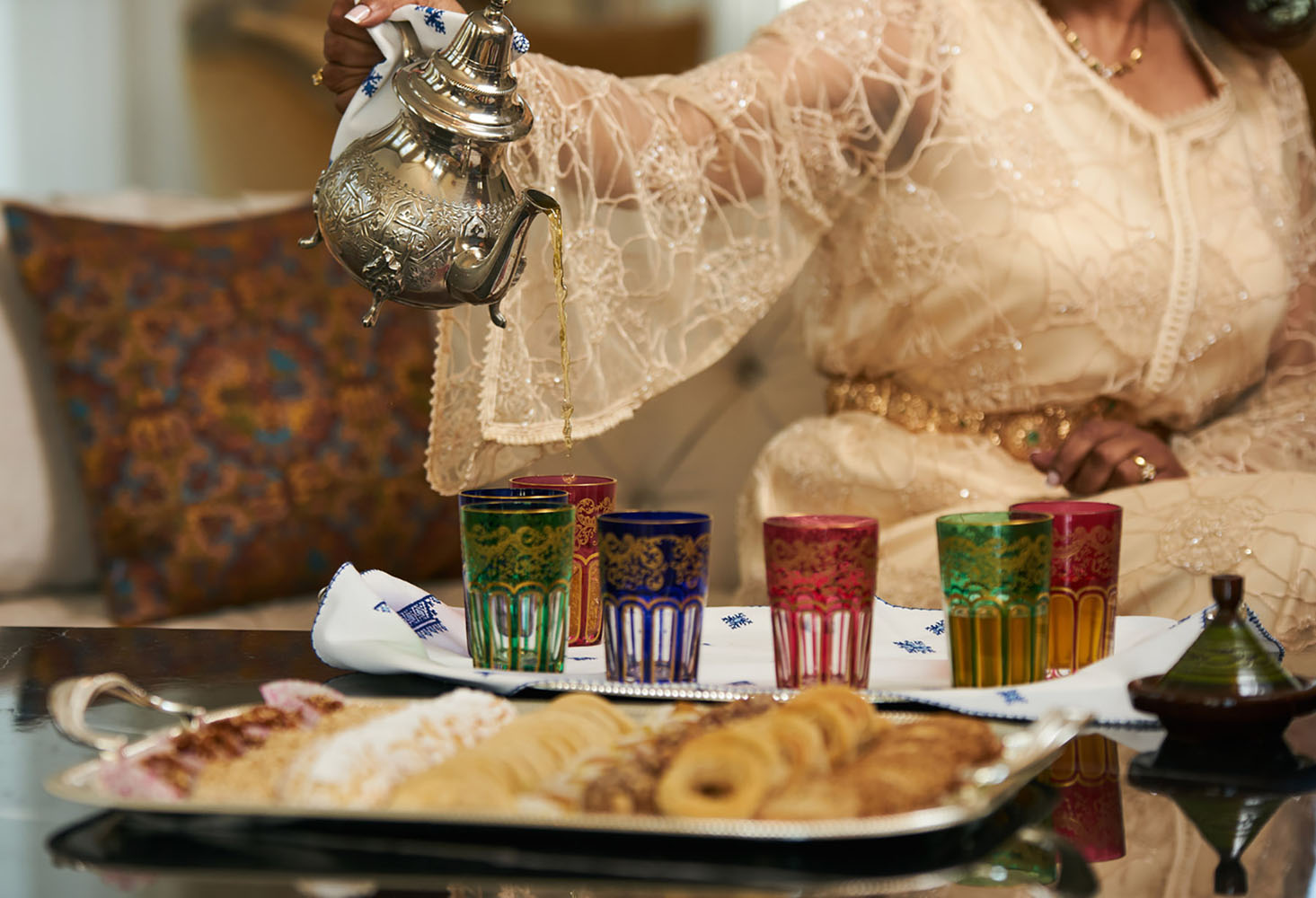 A woman Pours Moroccan Tea from Traditional moroccan Teapot into cups