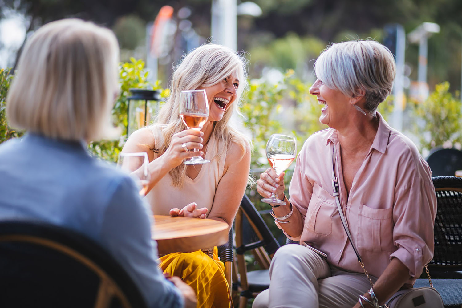 Women drinking wine and laughing at a restaurant