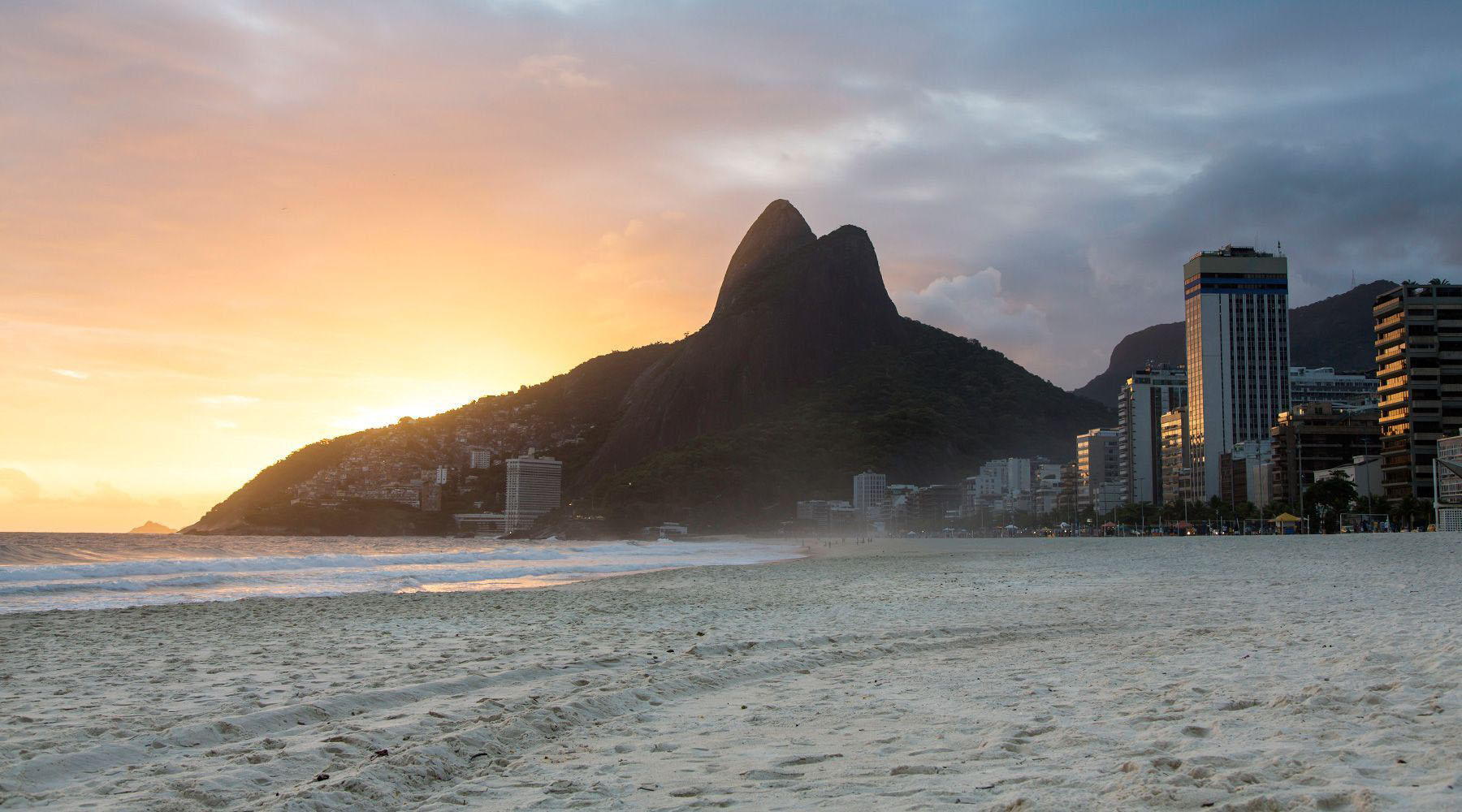 image of the copacabana beach in brazil with sand and cityscape
