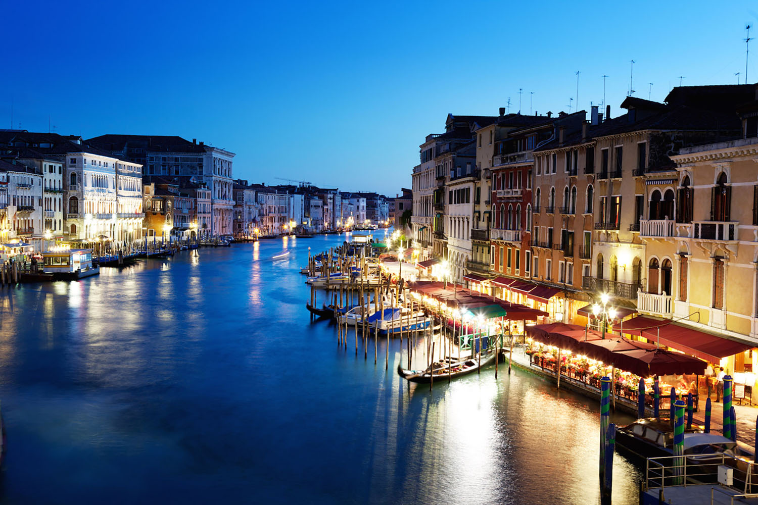A romantic canal filled with gondolas at night in Venice, Italy.